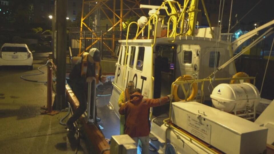 Trois hommes embarquent sur un bateau qui accoste au quai.