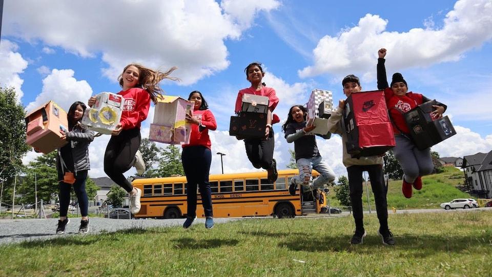 Des élèves présentent fièrement leurs sacs à dos équitables.