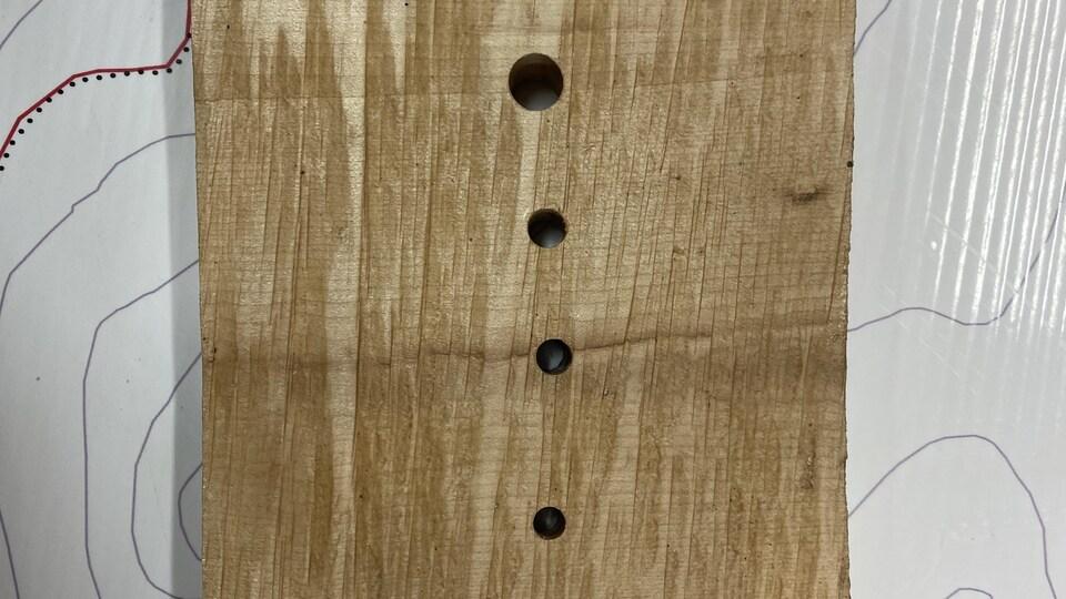 Planche de bois avec des trous à la verticale.