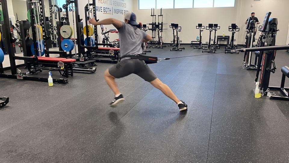 Eric Alarie fait un exercice avec un élastique attaché à la taille.