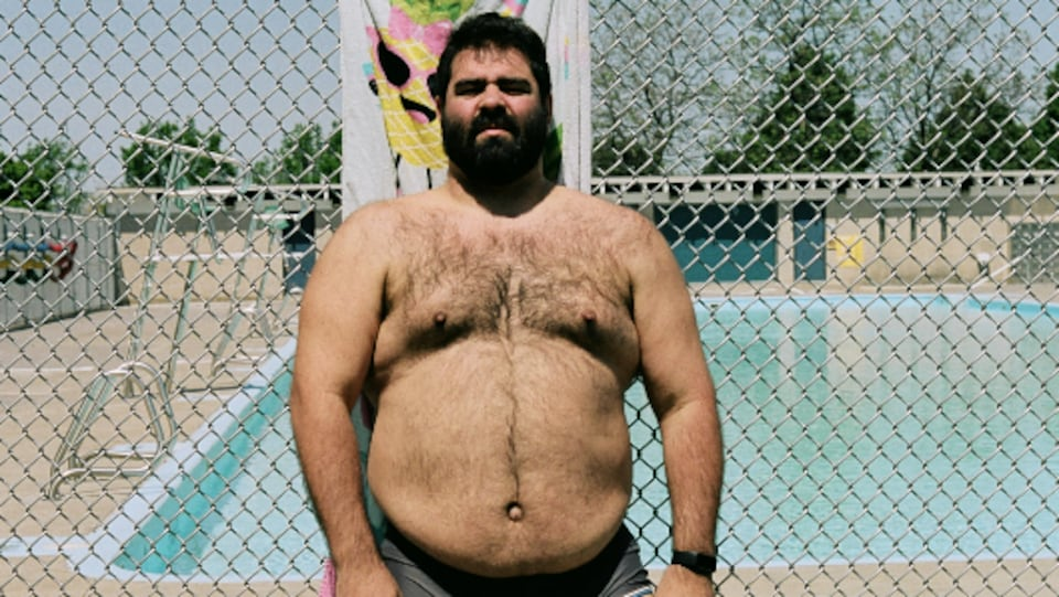 Un homme, en maillot, la poirtrine dévoilée, pose devant la clôture métallique d'une piscine publique.