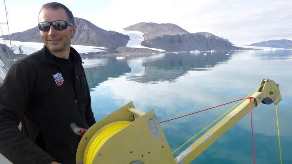 Éric Brossier tient un treuil à bord de son voilier.