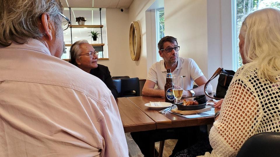 Éric Duhaime s'entretient avec des partisans autour d'une table.