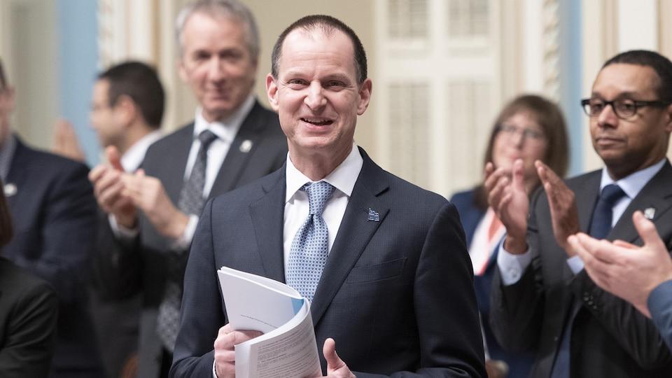 Le ministre tient le document du budget dans ses mains.