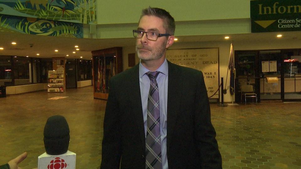 Eric Labelle se tient debout dans le hall d'entrée de la mairie de Sudbury.