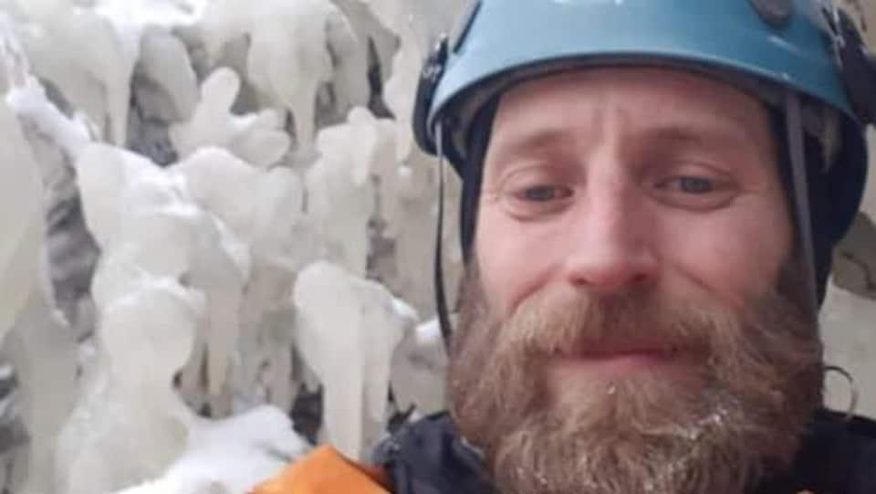 Un homme prend un égo-portrait dans son habit de spéléologie, devant la glace.