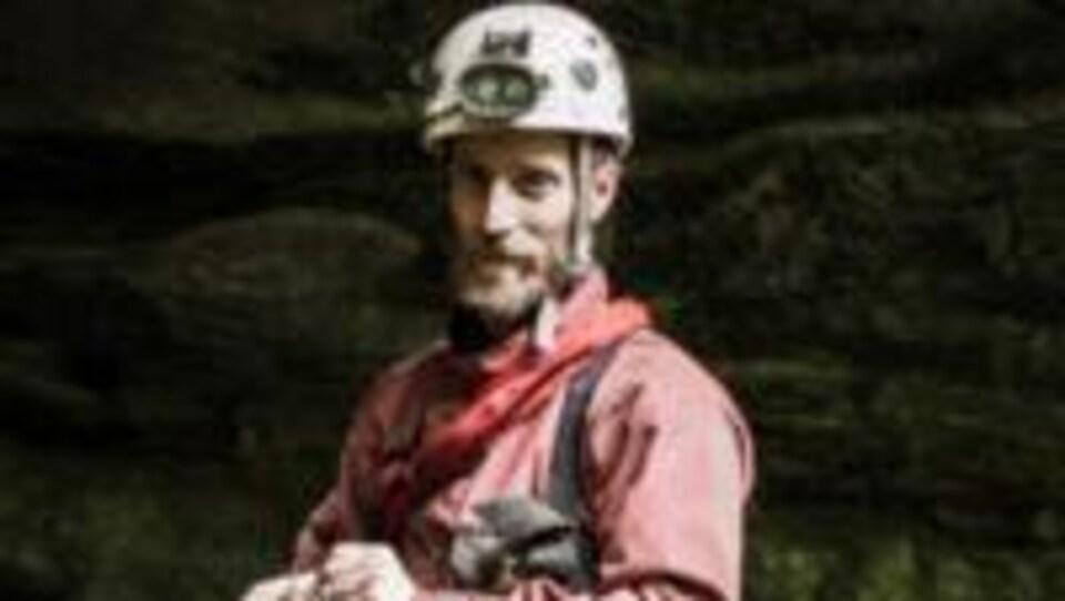 Un homme pose habillé avec de l'équipement d'escalade.