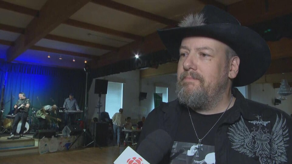 Un homme en entrevue, avec un chapeau de cowboy.