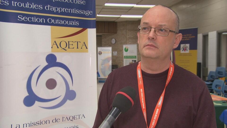 Éric Paradis devant la bannière l'Association québécoise des troubles d'apprentissage