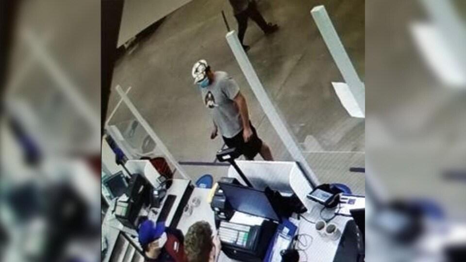 Un homme en t-shirt debout devant un comptoir.