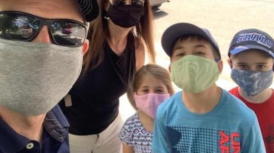 Des parents en compagnie de leurs trois enfants, tous masqués.