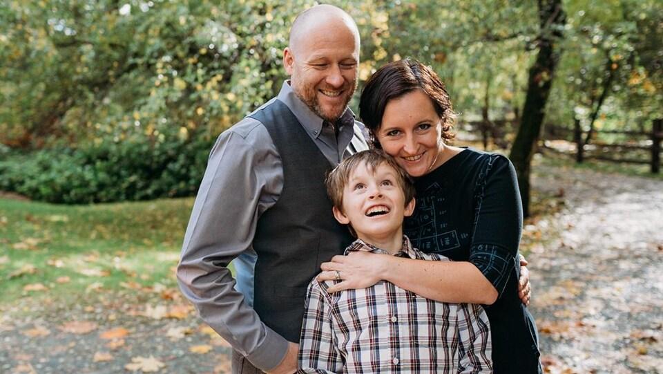 Un père, une mère et leur fils habillés élégamment, avec en arrière-plan, des arbres en flou.