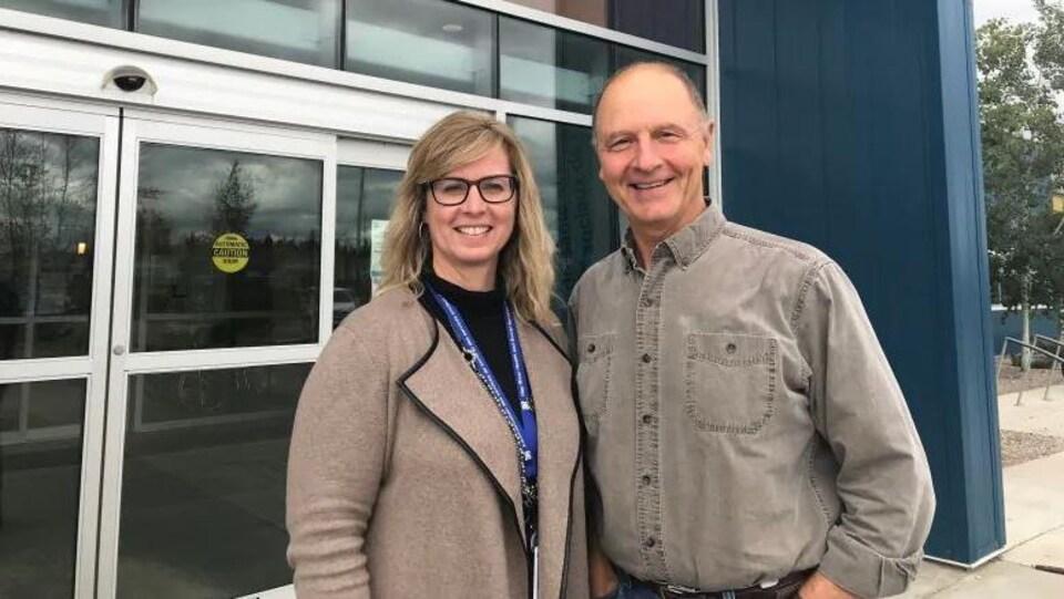 Plan moyen d'Erin Griffiths et de David Wilson debout côte à côte devant les portes d'un immeuble.