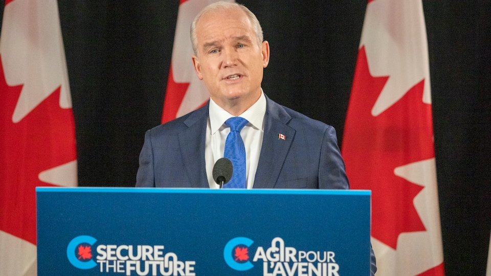 Erin O'Toole prononce un discours derrière un podium avec, derrière lui, des drapeaux du Canada.