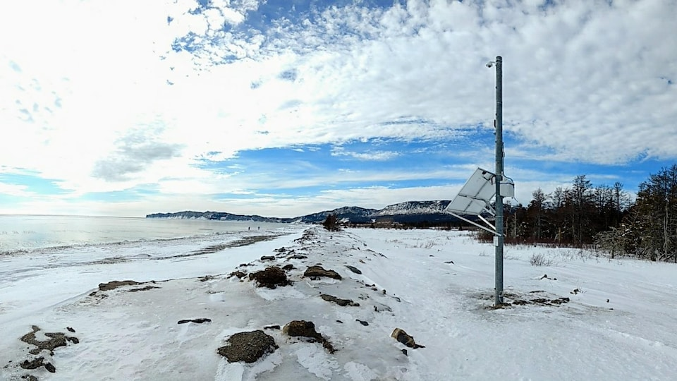 Des équipements de mesure sont installés sur un poteau près d'une berge enneigée.