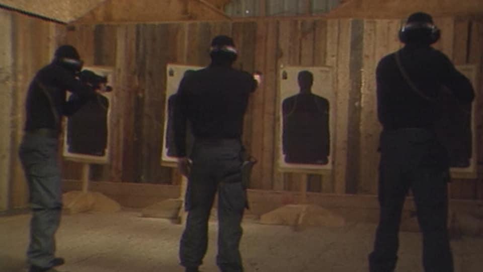 Trois policiers cagoulés tirent sur des cibles de papier.