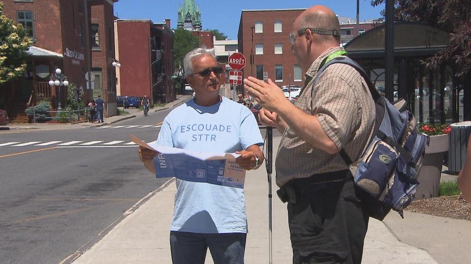 Homme vêtu d'un chandail « escouade STTR tenant une carte et parlant à un usager malvoyant.