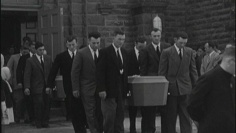 Des hommes transportent un cercueil.