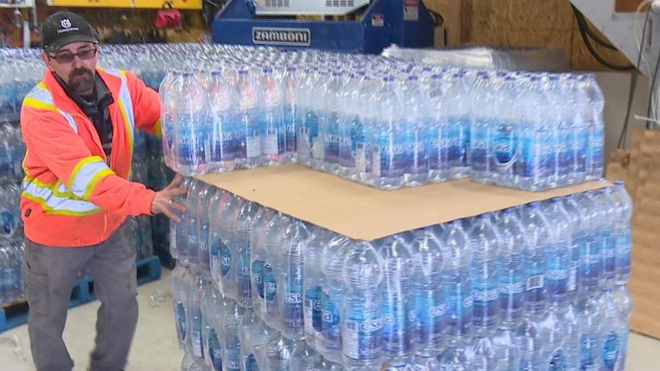 Un employé du garage municipal de St-Mathieu-d'Harricana, où la distrubution des caisses de bouteilles d'eau Eska.