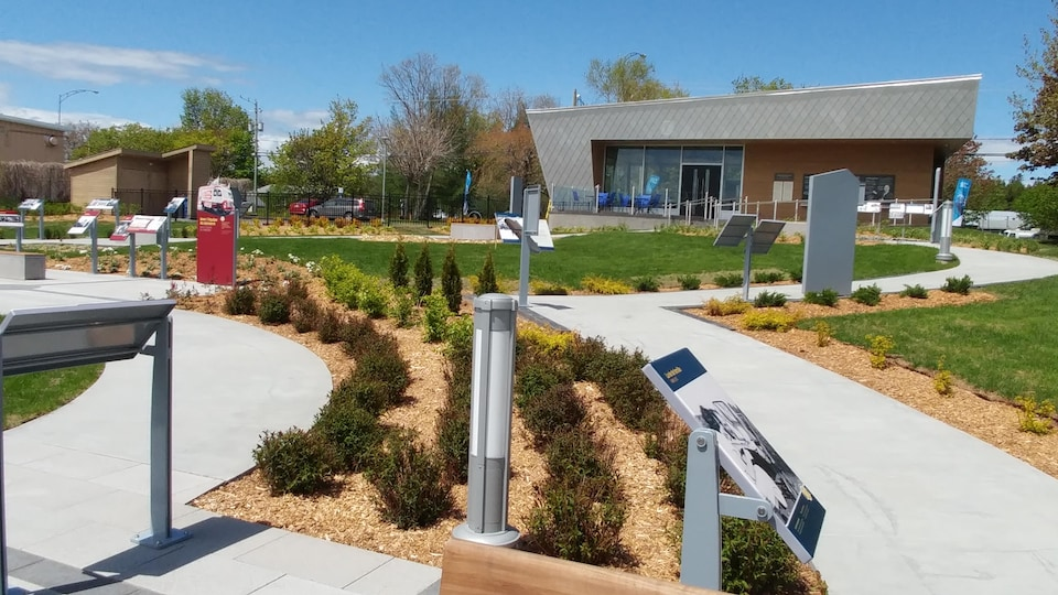 Devant le pavillon, un sentier de pierres blanches est aménagé entre des espaces gazonnés. Il est jonché de panneaux où l'on peut voir des photos et du texte.