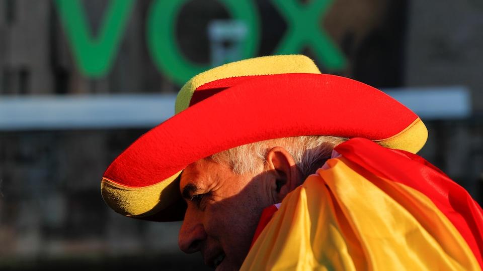Un partisan du parti d'extrême droite Vox porte un chapeau et une cape aux couleurs de l'Espagne.