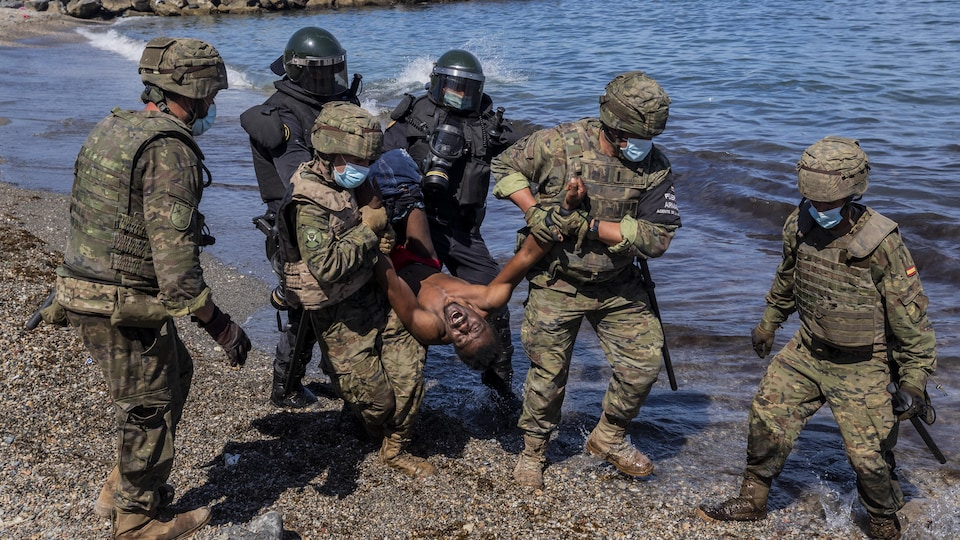 Six militaires soulèvent un migrant de terre sur une plage.