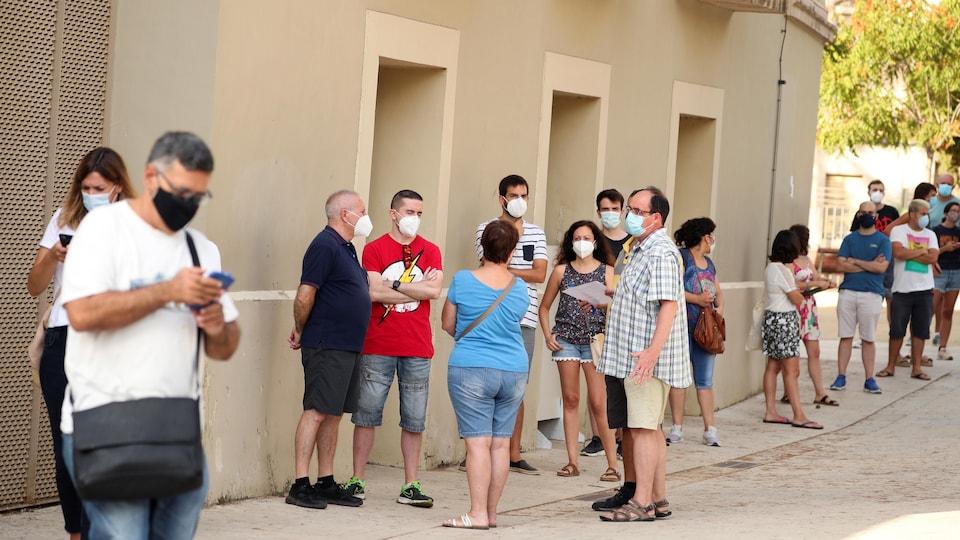 Des citoyens font la file pour le test de la COVID-19 près de Barcelone, en Espagne