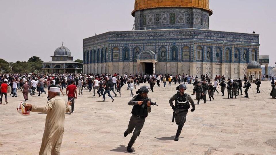 Des policiers armées et des civils courent dans tous les sens devant une immense mosquée.
