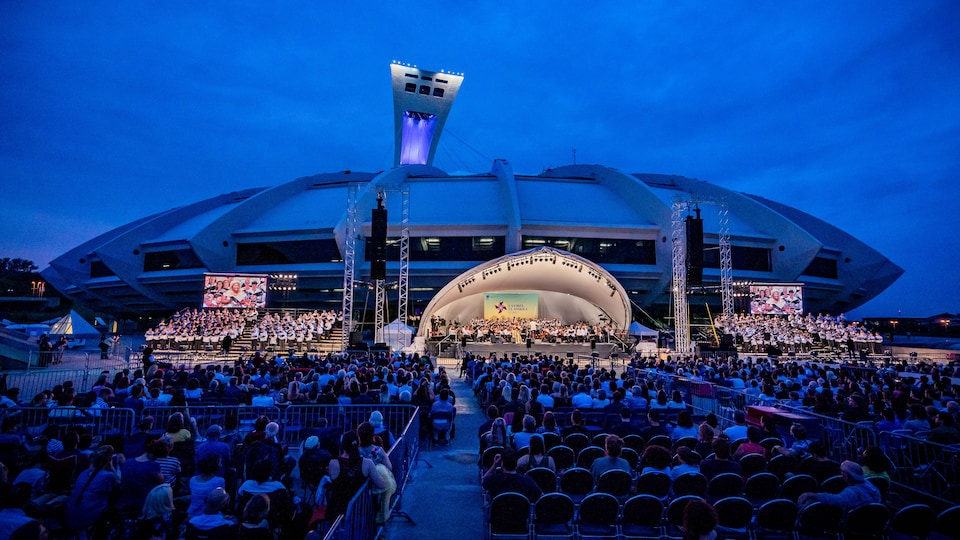 L'Orchestre symphonique de Montréal joue dans un amphithéâtre érigé devant le Stade olympique. Des milliers de spectateurs et spectatrices assistent au concert.