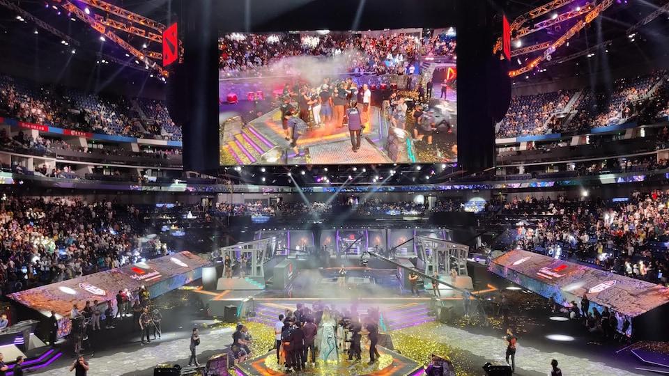 Vue d'ensemble sur le Mercedez-Benz Arena après la victoire de Team OG aux championnats internationaux de « DOTA 2 ». L'équipe célèbre et des confettis jonchent le sol.