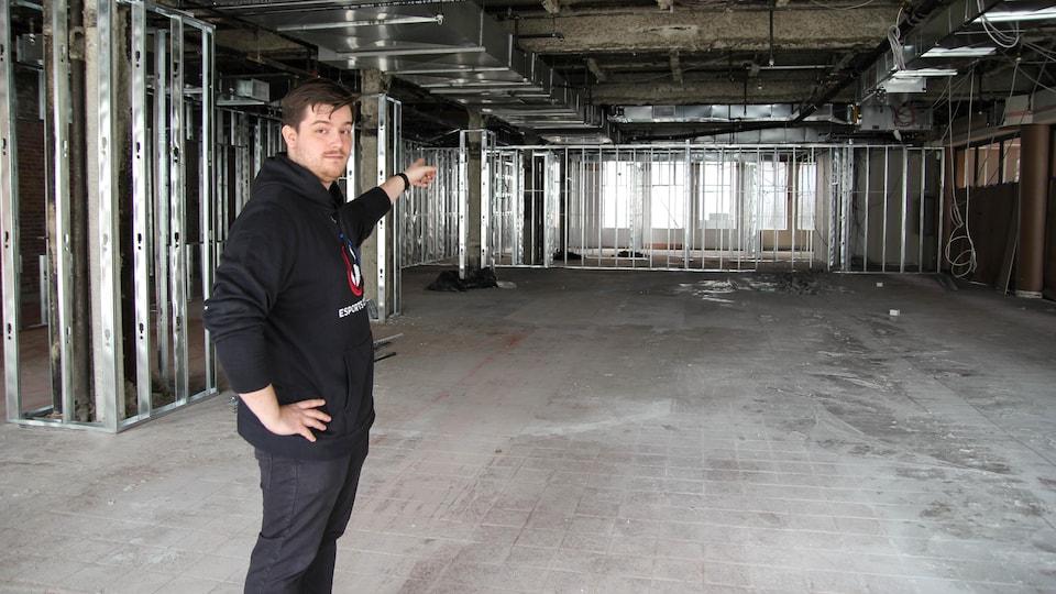 Anthony Côté est debout au centre du chantier de construction et pointe vers le fond de la salle.