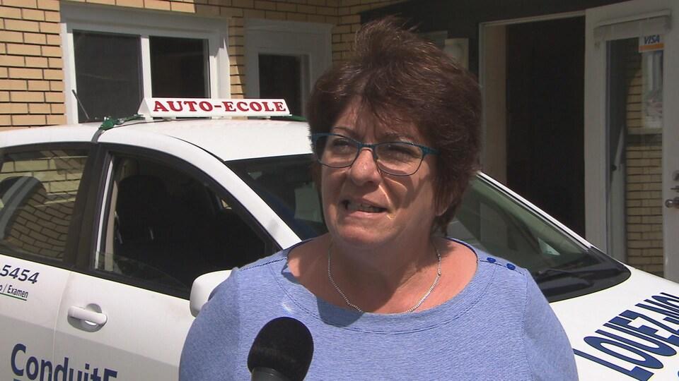 Estelle Rioux, instructrice en conduite automobile et présidente d'Asbestrie, devant l'une des voitures «Auto-École».