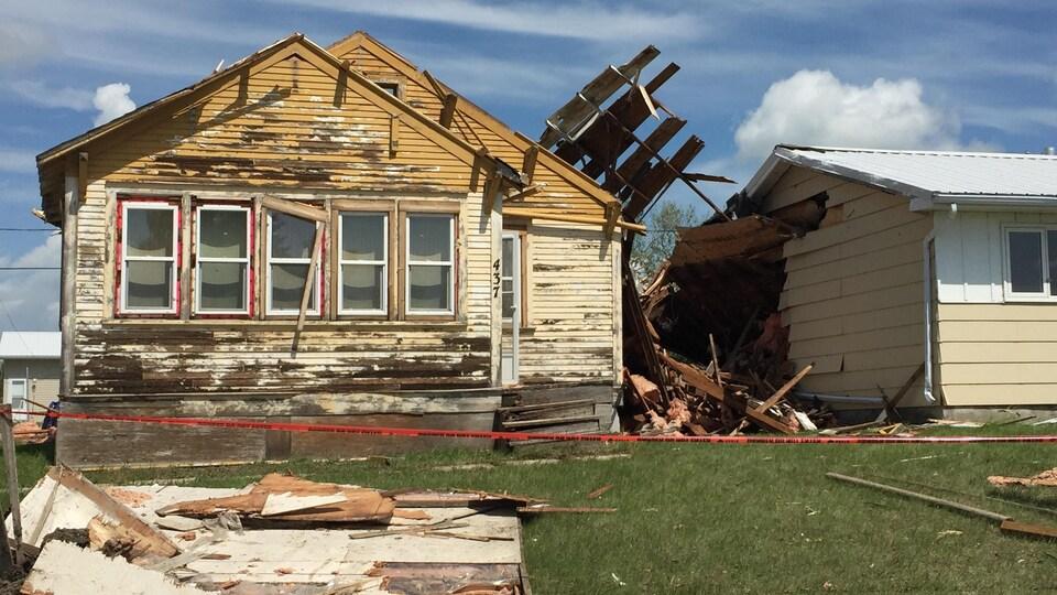 Une maison endommagée, avec des morceaux de façade arrachés par la tempête.