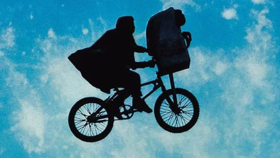 Petit garçon sur un vélo volant avec un extraterrestre dans son panier.