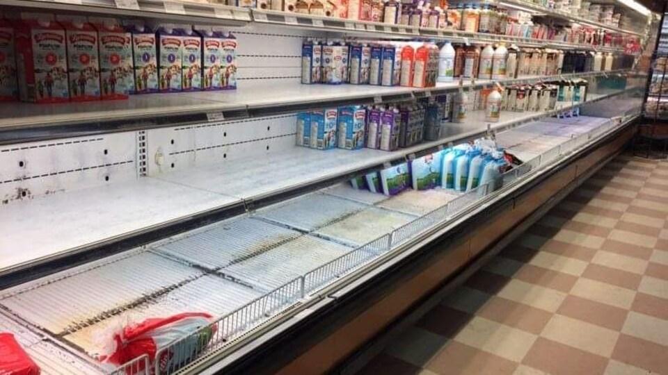 Des étagères de lait avec seulement quelques boîtes de lait.