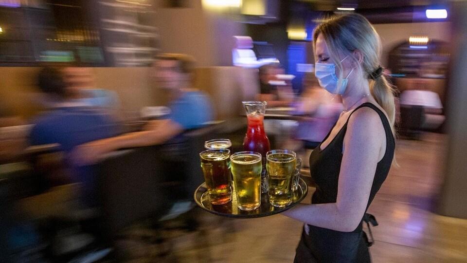 Une serveuse avec un masque sur le visage porte un plateau recouvert de boissons dans une salle de restaurant.