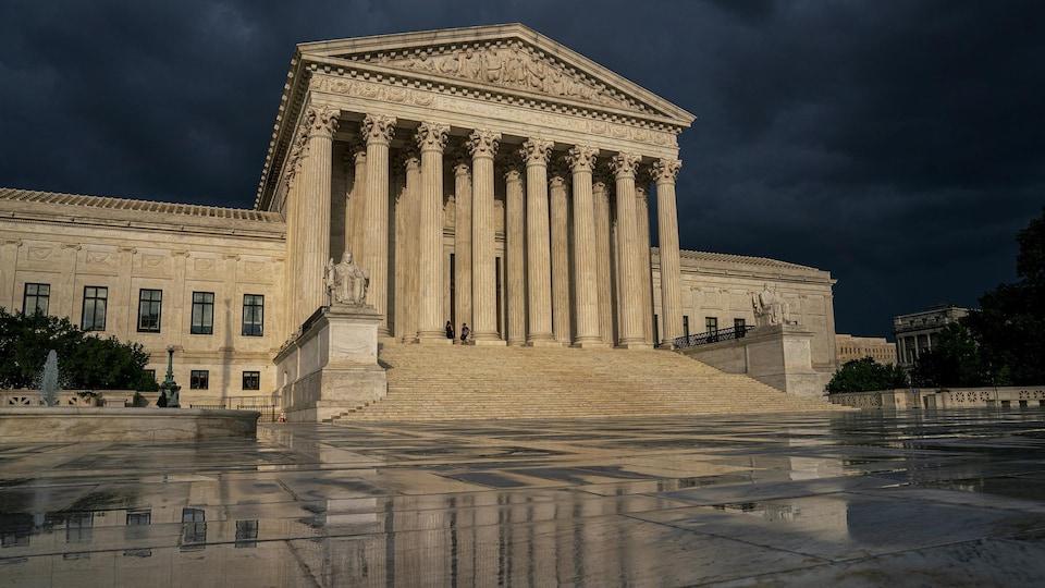 La Cour suprême des États-Unis vue en contre-plongée, sous un ciel nuageux.