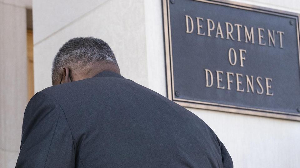 Lloyd Austin passe devant un panneau où est écrit « département de la Défense ».