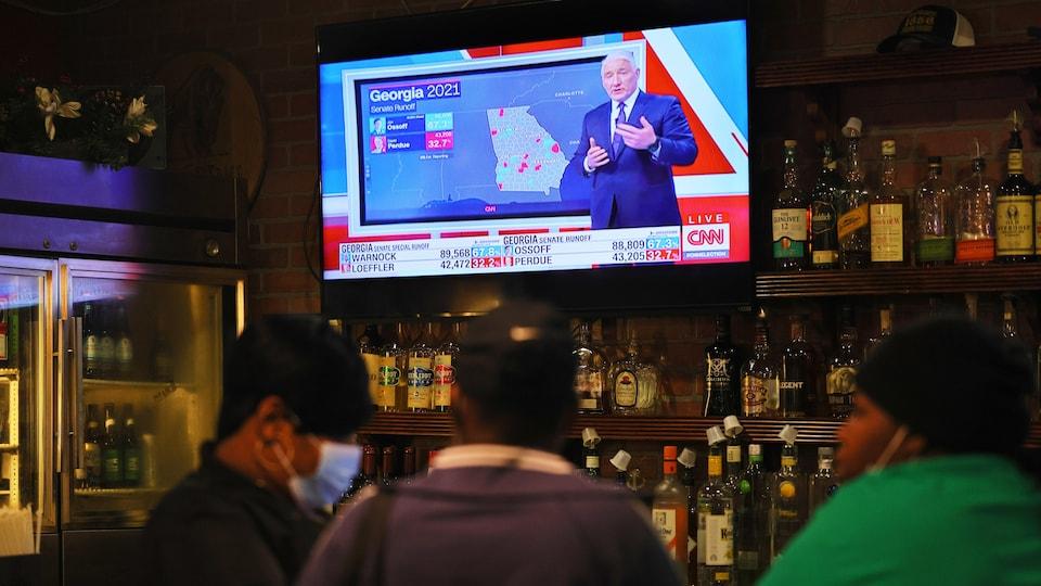 Des gens sont assis à un bar où une télé présente les résultats des courses au Sénat.