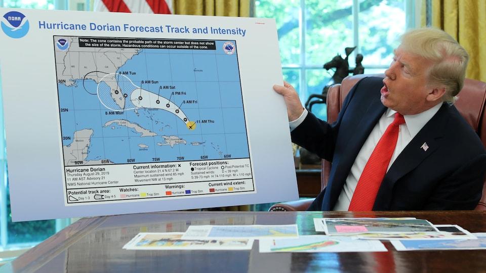 Donald Trump dans le bureau ovale présente une carte.