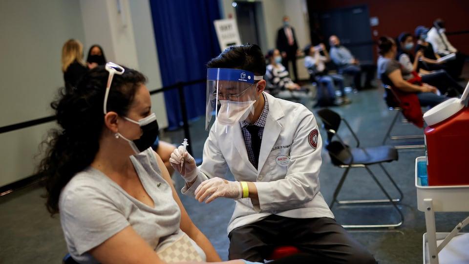 Une femme qui porte un masque reçoit le vaccin Johnson & Johnson.