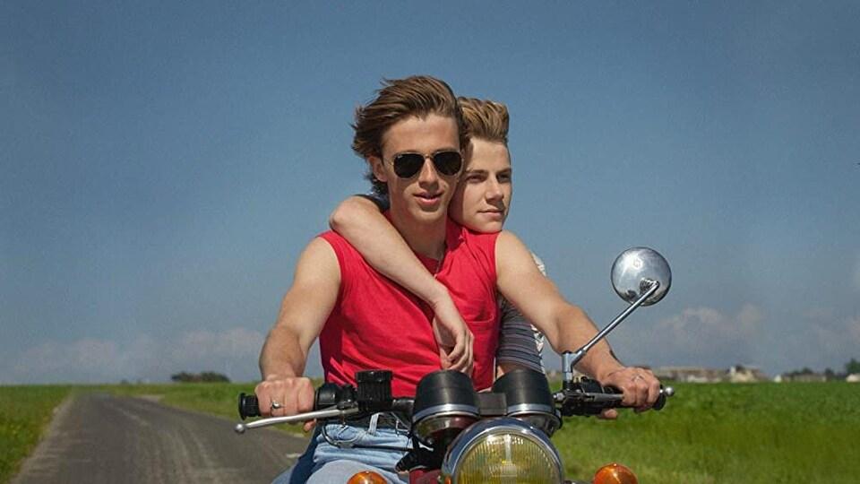 Deux jeunes sont sur une moto, cheveux au vent, sur une route de campagne.