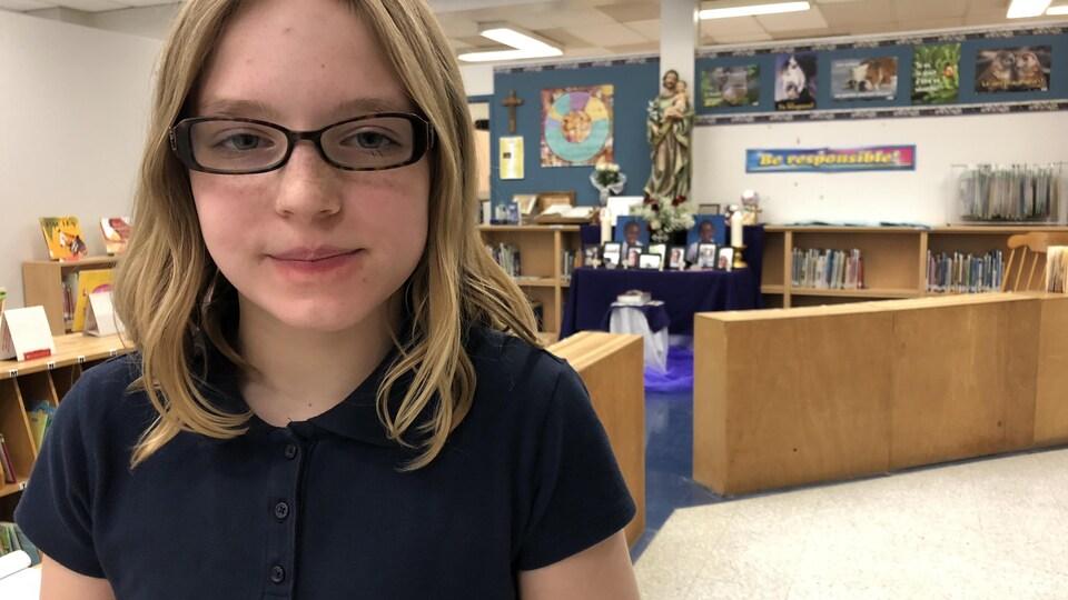 Une petite fille regarde la caméra. On voit le mémorial derrière elle.