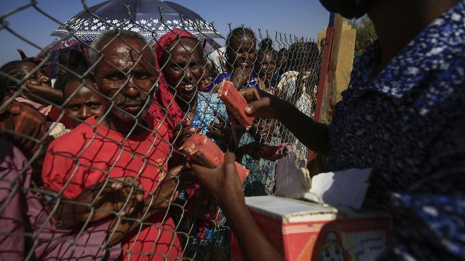 Des réfugiés, femmes, enfants et personnes âgées, se trouvent derrière des grillages, tandis qu'on leur distribue de la nourriture.