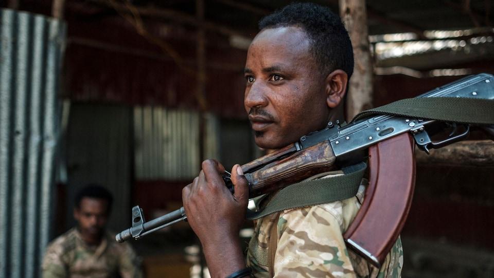 Un soldat tient un fusil mitrailleur.