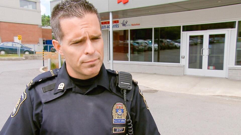 Étienne Doyon, porte-parole du Service de police de la Ville de Québec, en entrevue devant une succursale d'un établissement financier.