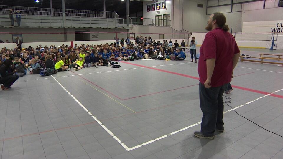 Étienne Gravel se tient debout dans un gymnase devant une assemblée de jeunes assis devant lui.