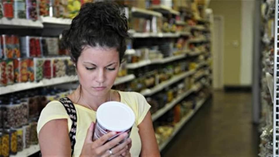 Une femme examine l'étiquette d'une conserve dans une épicerie.