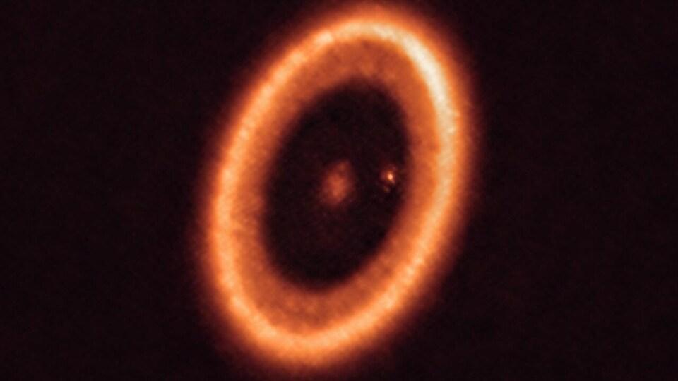 Un point brillant (une étoile) dans le noir de l'espace. Ce point est entouré d'un anneau brillant (de la matière). Entre le point et l'anneau se trouve un point plus petit, une exoplanète, autour de laquelle orbite de la matière.