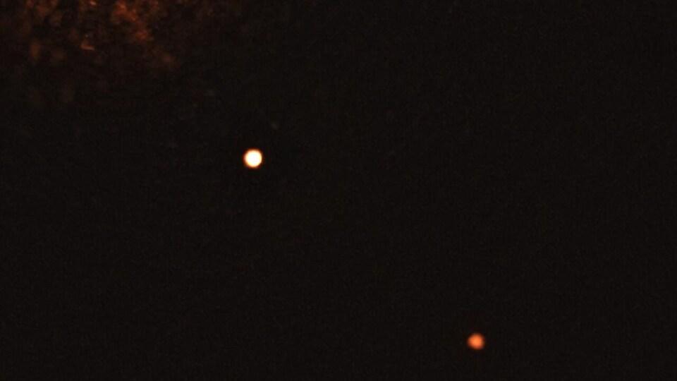 L'étoile, un point brillant sur fond noir, est entourée de deux points un peu moins brillants, les planètes.